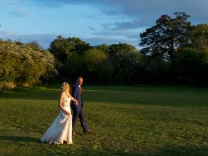 Bride and groom walk across field in spring evening sunshine at Thre Three Tuns, Bransgore