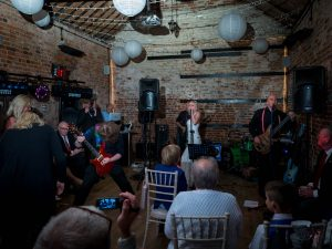 Lead guitarist riffs as bride sings with her band at The Three Tuns, Bransgore