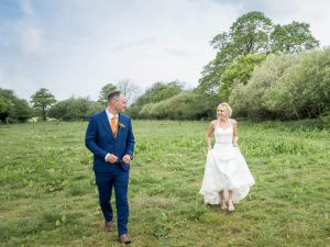 Bride and groom walk across field behind The Thre Three Tuns, Bransgore
