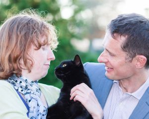 Woman with ginger hair cradling a black cat as man in blue jacket looks on