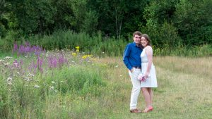 Man in blue shirt and woman in white dress stand close together and smile in wildflower meadow