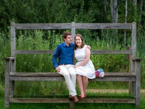 Man in blue shirt and woman in white dress sit close together on giant garden bench