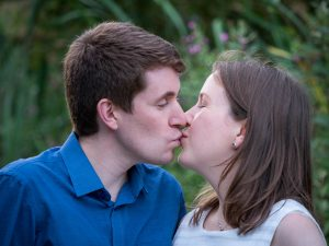 Man in blue shirt and woman in white dress kiss
