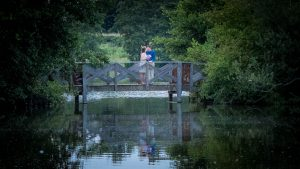 Woman in white dress and man in blue shirt kiss on wooden bridge