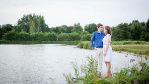 Man standing with arm around woman beside the lake on a summer evening in Eastleigh Lakeside Country Park