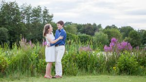 Woman and man embrace on lakeside meadow