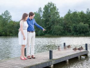 Man in blue shirt with woman in white dress points to ducks on lakeside jetty
