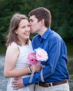 Man in blue shirt kisses woman in white dress on the cheek as she holds pink peonies