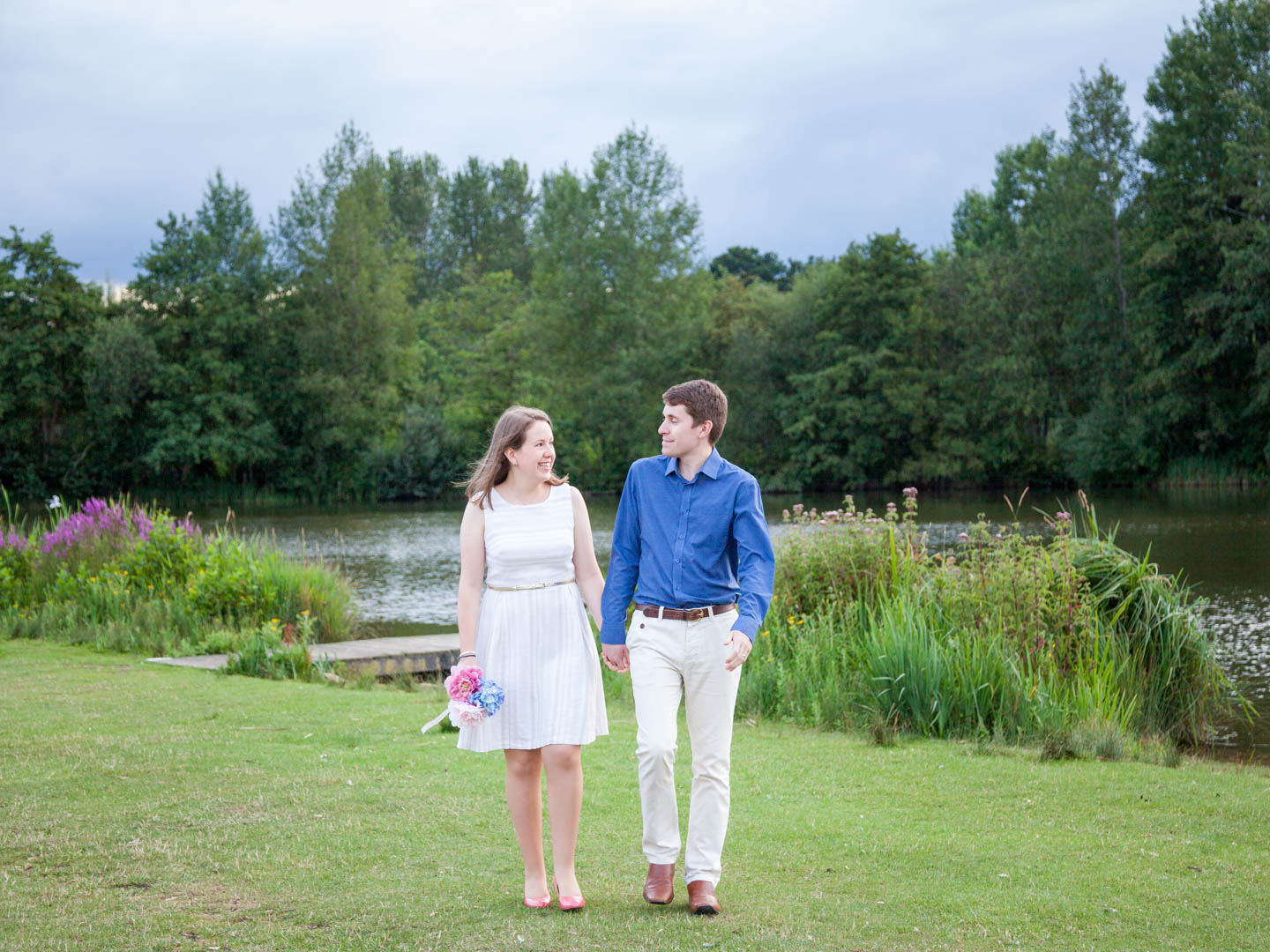 Couple walk hand-in-hand beside lake on a summer's evening in Eastleigh Lakeside Country Park