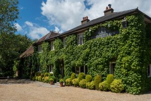 The Mill at Gordleton on a summer's day, its facade clad in ivy