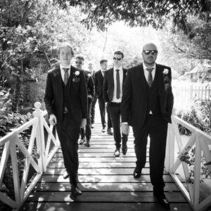 Groomsmen strike Reservoir Dogs pose while crossing a bridge at Gordleton Mill wedding