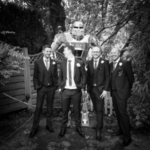 Groomsmen in front of a robot in the garden at a Gordleton Mill wedding