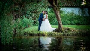 Couple kiss beside the lake at their Gordleton Mill wedding