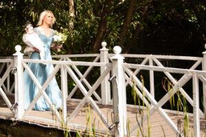 Bridesmaid crosses ornamental bridge with baby at a Gordleton Mill wedding