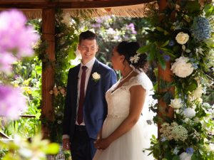 Bride and groom in a flower bower during their Gordleton Mill wedding