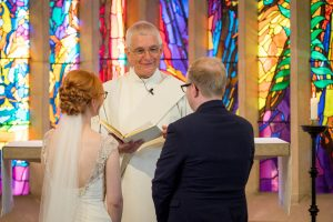 Priest addresses the bride and groom during their Chandler's Ford Roman Catholic church wedding