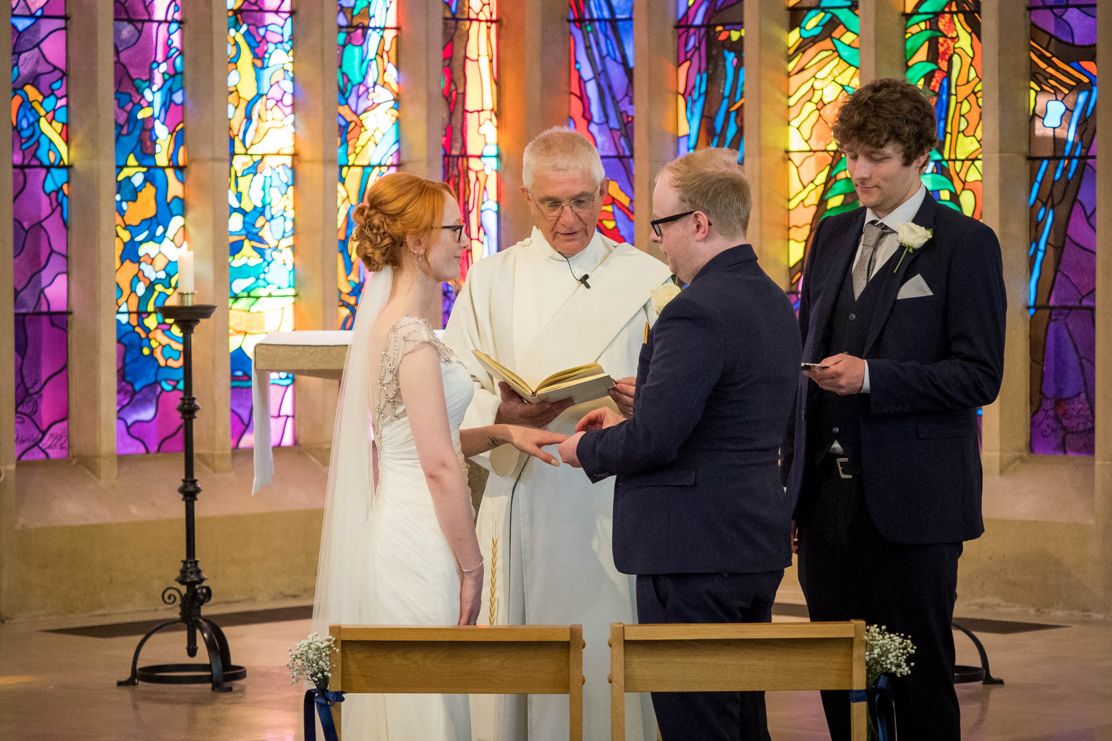 Bride receives her ring from her groom during their Chandler's Ford Roman Catholic church wedding