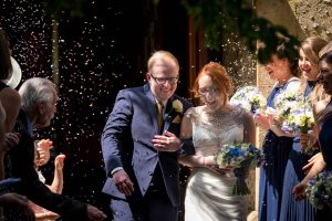 Bride and groom enjoy a confetti shower outside Chandler's Ford Roman Catholic church