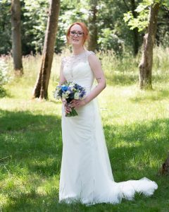 Bride holds bouquet in the grounds of  Marwell Hotel  during her wedding reception