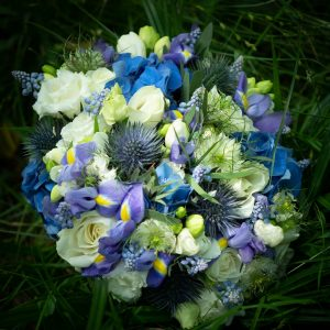 Bridal bouquet  of  white roses, irises and thistles on a bed of grass