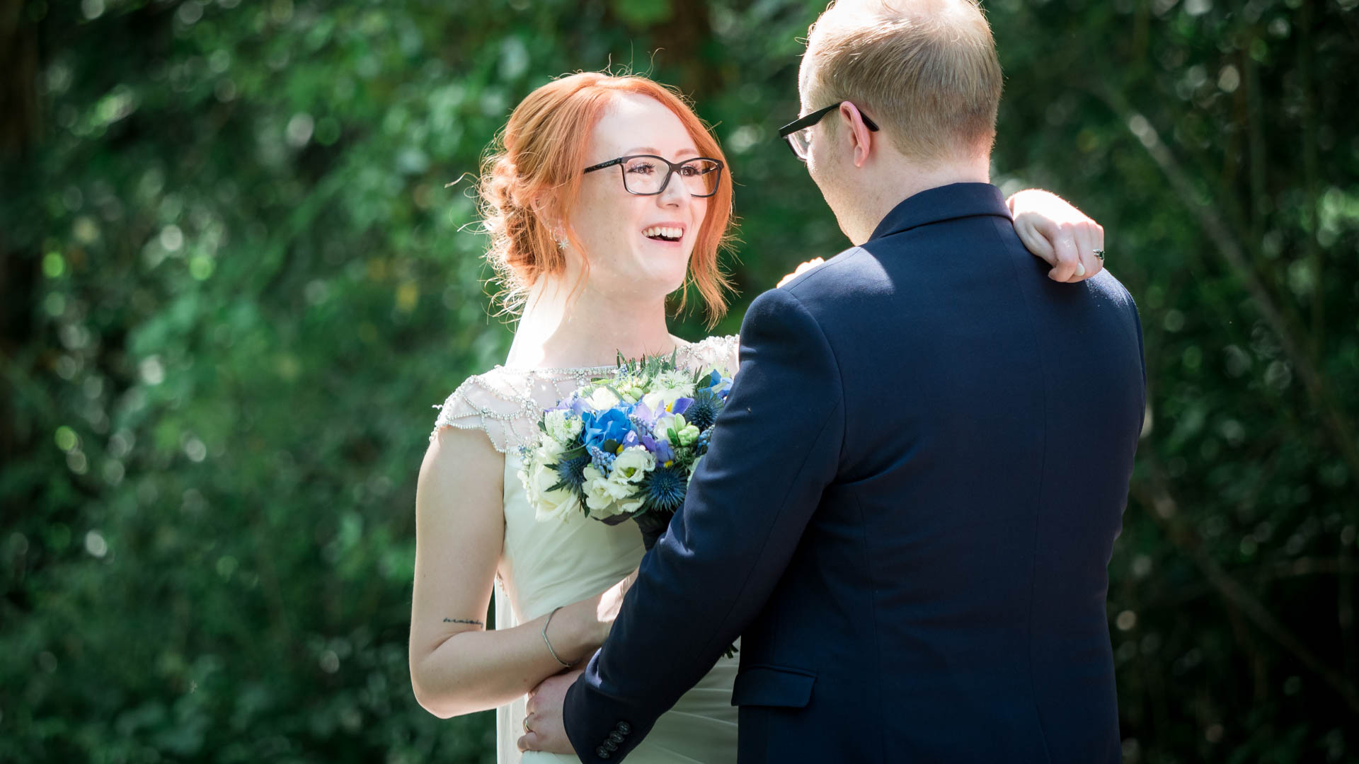 Backlit bride smiles at groom outside during their Marwell Hotel wedding reception