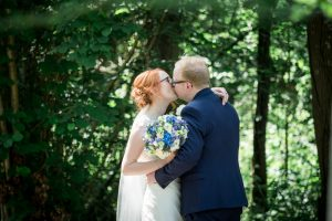 Bride and groom kiss in a woodland glade during their  Marwell Hotel wedding reception