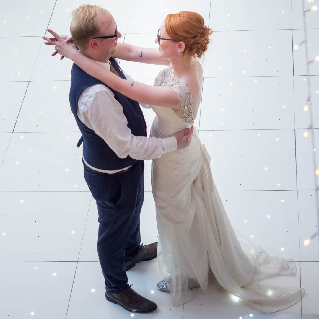 Bride and groom on a white dance floor at their  Marwell Hotel wedding reception