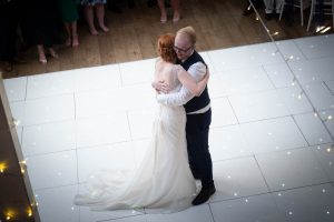 Bride and groom embrace at the end of their Marwell Hotel wedding reception
