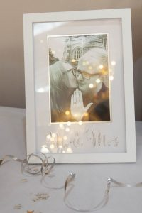 Fairy lights reflected in a framed portrait of the bride and groom