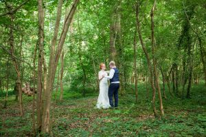 Bride and groom in a woodland glade during their  Marwell Hotel wedding reception