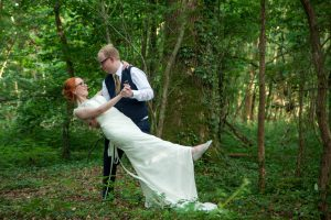 Groom dips bride in a woodland glade during their  Marwell Hotel wedding reception