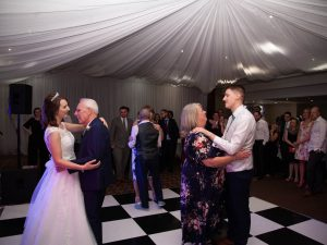 Bride dances with her father while groom dances with his mother on checkerboard floor