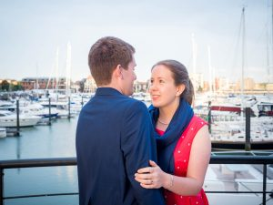 Woman in red dress smiles at man in dark suit in front of yacht marina