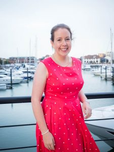 Woman smiling in red polka dot dress with Ocean Village yacht marina in the background