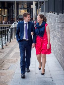 Man in dark suit and woman in red dress smile while walking along quayside