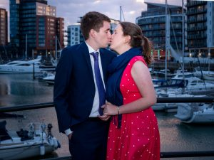 Woman in red dress and man in dark suit kiss in front of yacht marina