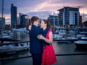 Woman in red dress smiles at man in dark suit in front of yacht marina after sunset