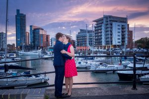 Woman in red dress and man in dark suit kiss in front of yacht marina after sunset