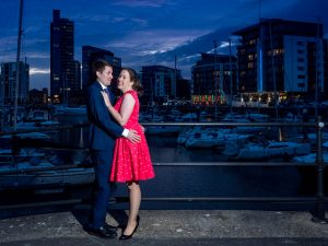 Woman in red dress and man in dark suit at sunset in front of yacht marina