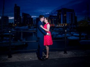 Woman in red dress and man in dark suit embrace in front of yacht marina after sunset