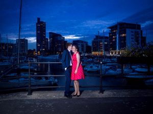 Man in suit kisses woman in red dress  in front of yacht marina at dusk