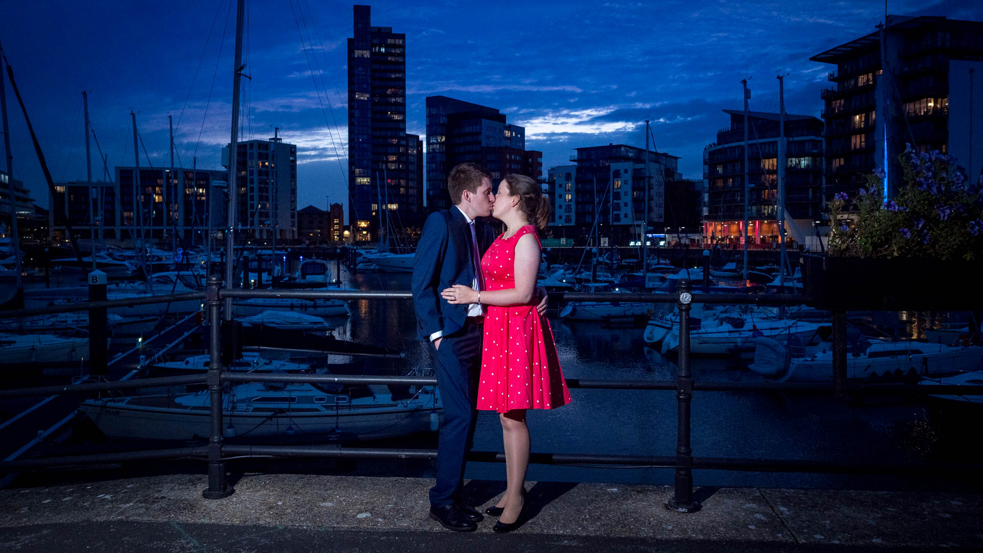 Woman in red dress and man in dark suit kiss in front of yacht marina at dusk