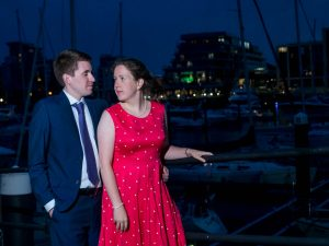 Woman in red dress and man in dark suit in front of yacht marina