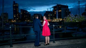 Woman in red dress and man in dark suit in front of yacht marina at dusk