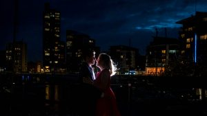 Woman in red dress and man in dark suit in front of yacht marina backlit by flash at night