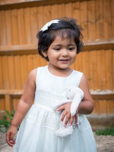 Indian girl toddler wearing a white dress in a back garden