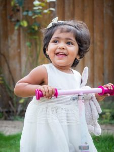 Indian girl toddler on pink scooter in back garden