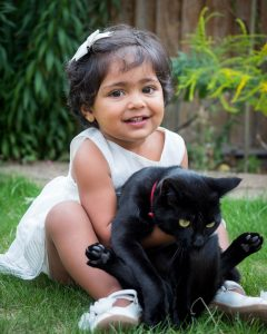 Indian girl toddler in white dress with black cat in back garden