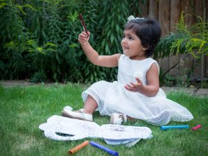 Indian girl toddler in white dress with colouring book sitting on lawn