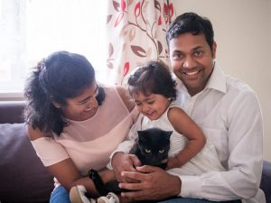 Indian father, mother, young daughter and black cat